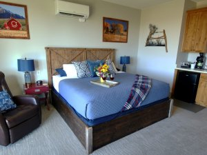 King-sized bed next to kitchenette and chair
