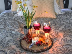 Plate of wine and snacks on bed