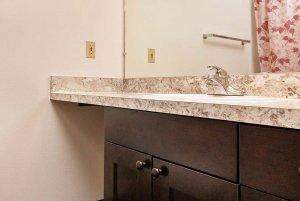 bathroom sink and wood cabinets