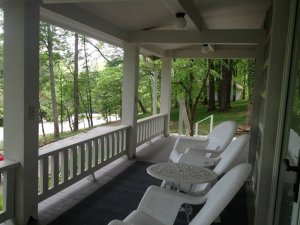 Seats on porch looking past railing