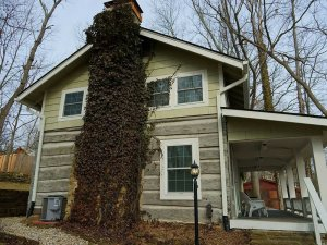 Mossy stone chimney going up cabin from outside