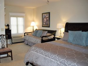 King-sized bed next to lamps and a trundle bed