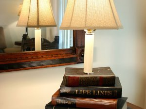 Lamp ontop of stack of books on a desk