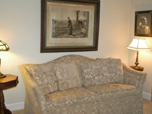 Sofa between lamps and under picture frame