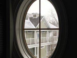 Snowy house through attic window