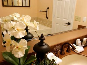Flowers next to mirror and sink in bathroom