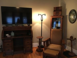 Chair and footstool next to television and lamp