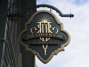 Upper rooms sign held infront of clear sky