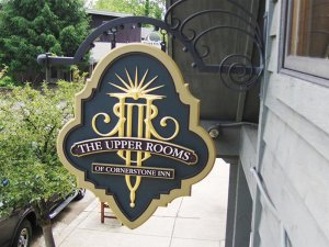 Upper rooms sign hung from decorative metal hanger
