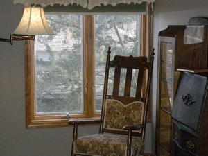 Rocking chair infront of window in bedroom