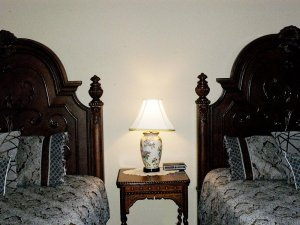 Lamp on endtable between two queen-sized beds
