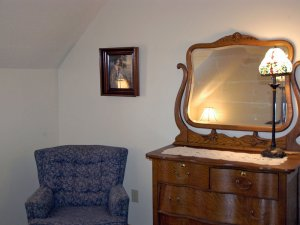 Reclining chair and vanity in corner of the room