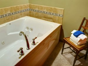 Two-person whirlpool tub in bathroom next to chair and towels