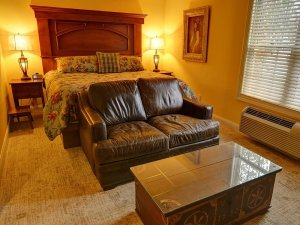 Leather couch and coffee table at end of king-sized bed