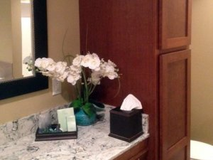 Flowers in small vase next to toiletries on bathroom counter