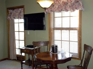 Television and windows above table and chairs