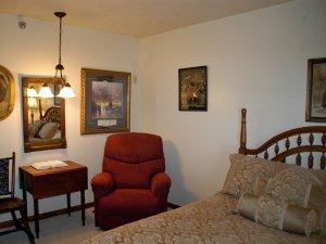 Reclining chair sittin in corner of bedroom