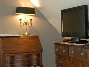 Television next to dresser with lamp on it