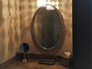 Large mirror and smaller mirror above sink in bathroom