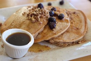 Pancakes with granola, blueberries, and syrup