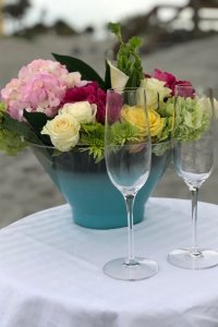 Two wine glasses on white tablecloth next to flowers