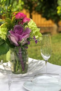 Wine glass next to a vase of flowers on a table