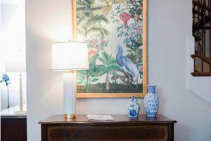 Vases and lamp on counter below painting