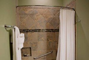 Shower next to towel rack in bathroom