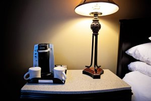 Coffee maker and lamp on bedside table