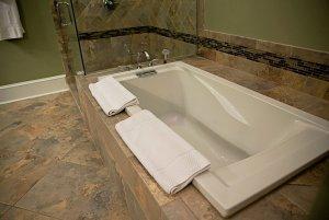 Towels folded by bathtub in bathroom