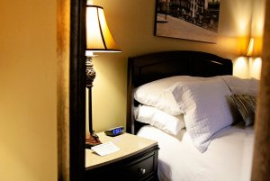 Lamp and clock next to pillows on bed