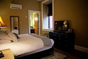 Bed, television, and bathroom door in bedroom