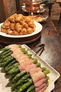 Bacon-wrapped asparagus next to croissants