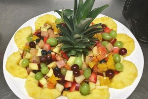 Fruit dish with pineapple slices around it
