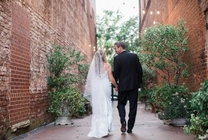 Bride and groom walking down alley with shrubery