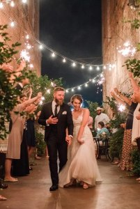 Bride and groom walking down alley with fairy lights