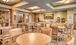 Dining room with tables, chairs, and breakfast bar