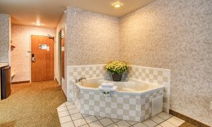 Bathtub with flowers and towels in corner of room