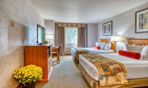 Queen beds across from television and cabinet