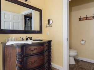 Sink countertop below mirror and next to toilet room