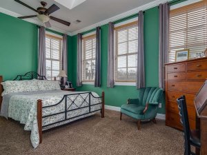 King-sized bed next to chair and dresser in bedroom