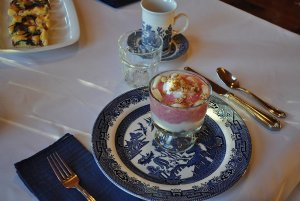 Glass cup filled with yogurt and granola set on plate