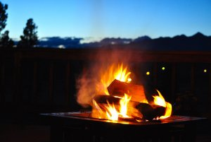 Logs burning in outdoor fireplace on patio