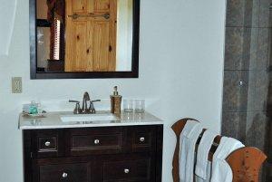 Sink below mirror and next to towel rack