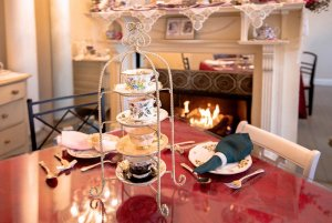 Teacups set in display tower on table infront of fireplace