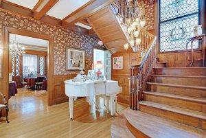 Grand piano between staircase and doorway to dining room