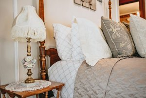 Lamp next to bed with decorative pillows