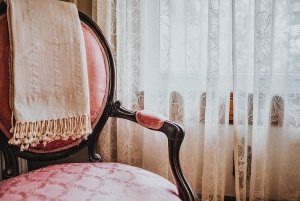 Blanket laid on cushoined wood chair by window