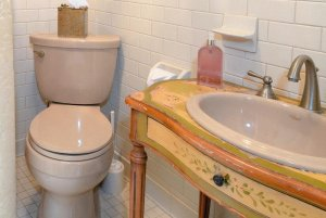 Toilet in corner of bathroom next to sink