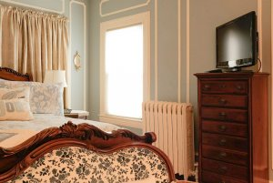 Queen-sized bed next to window, space heater, and drawers